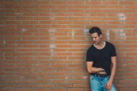 lean back: Stylish casual man lean back brick wall. Stock Photo