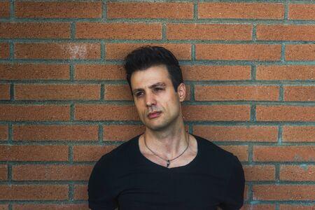 lean back: Stylish casual serious man lean back brick wall. Stock Photo