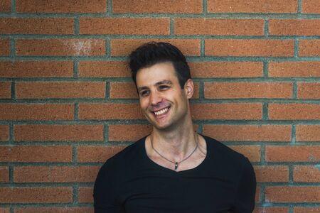 lean back: Stylish casual smiling man lean back brick wall. Stock Photo