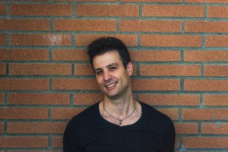 lean back: Stylish casual happy man lean back brick wall.