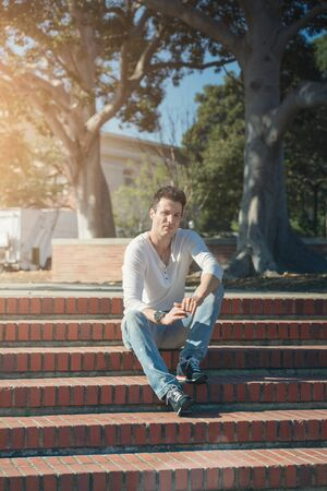 Stylish casual and serious man sitting on stairs