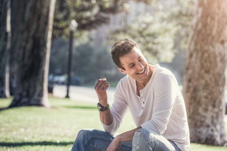Handsome casual happy man sitting in park, looking away.