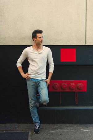 lean back: Handsome casual serious man lean back wall, looking away.