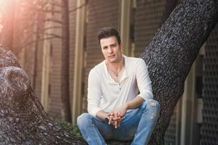Stylish casual serious man sitting on tree.