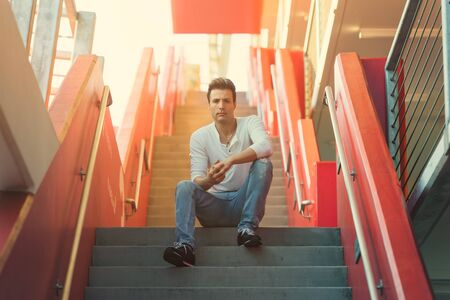 Stylish casual man sitting on stairs.