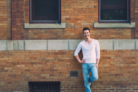 lean back: Stylish casual and happy man lean back brick building. Stock Photo