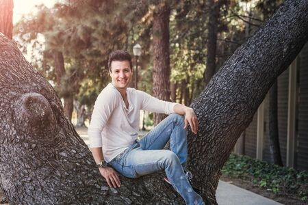 Handsome casual happy man sitting on tree.
