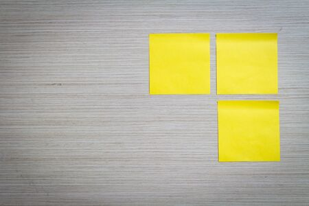 Yellow sticky note attach to a wooden wall photo