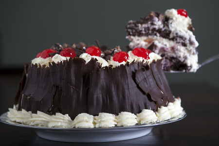 Chocolate cake with cream and cherries, being served. photo
