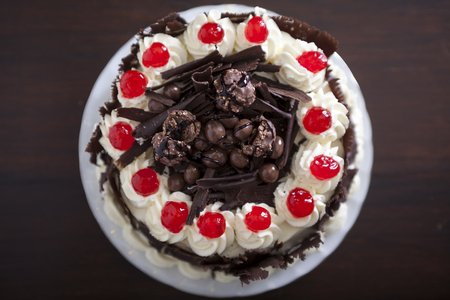 Chocolate cake with cream and cherries, from above. photo