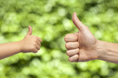 manos: father and son hands giving like on green background Stock Photo