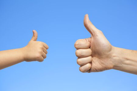 manos: father and son hands giving like on blue sky background
