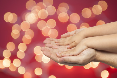 father and son holding hands on red christmas lights background Stock Photo