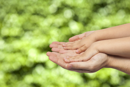 father and son holding hands on natural green background