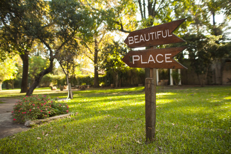 wooden garden sign reading Beautiful Place, pointing down the path Stock Photo