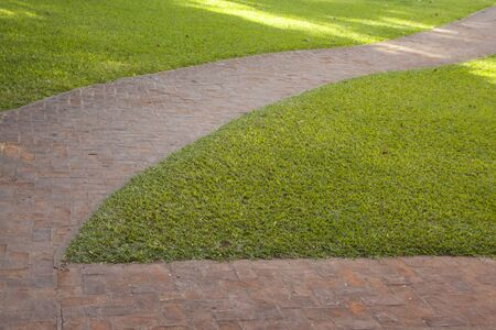 Curved red brick walkway with green grass around it