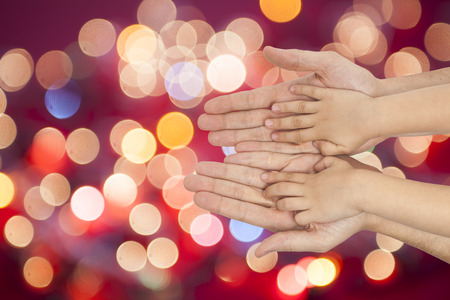 father and son holding hands on multicolored christmas lights background