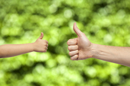 father and son hands giving like on natural green background