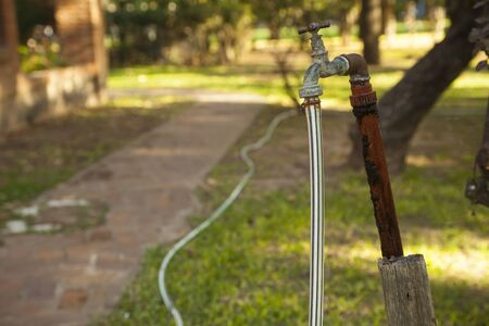 Old rusty water tap with hose in garden