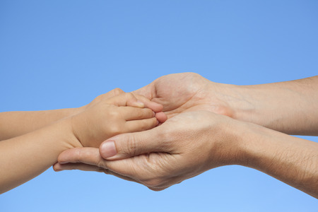 manos: father and son holding hands on a blue sky background