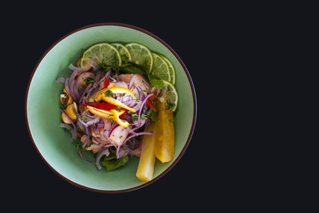 black dish: Salmon peruvian ceviche, with purple onion on black background. Served with pineapple and lime.