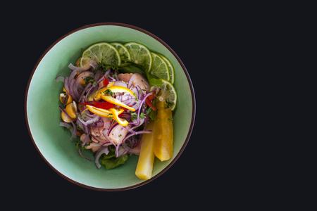Zalm Peruaanse ceviche, met paarse ui op zwarte achtergrond. Geserveerd met ananas en limoen.