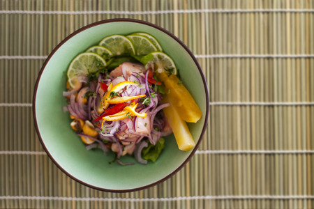 Salmon peruvian ceviche, with purple onion on bamboo mat. Served with pineapple and lime. Stock Photo