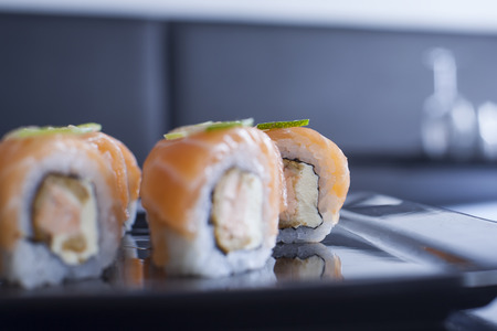 Sushi roll with cream cheese and fried salmon. Topped with raw salmon and lime. Close up.