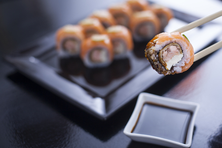 sushi restaurant: Sushi roll with cream cheese and fried salmon. Topped with raw salmon and lime. Being picked up with chopsticks from soy sauce, with more rolls on black dish in the background Stock Photo