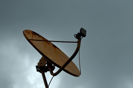 sattelite: Battered old television Satellite reciever under cloudy sky