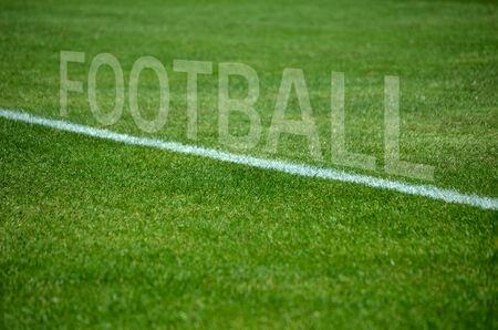 Text football on green grass with white lane photo