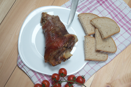 hock: Photo of arranged ham hock or pork knuckle from a pig with knife bread and cherry tomatoes on wooden desk. Smoked dried meat food. Food photo View from above.