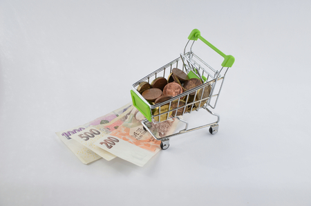 Glossy and colorful coins with banknotes in the shoping cart. Bank product. Financial item. Isolated background Stock Photo