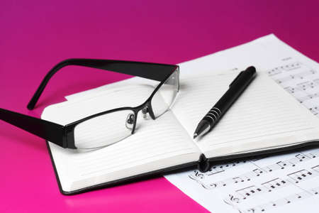 Close up of reading glasses pen and open diary laid on printed piano sheet isolated on pink background