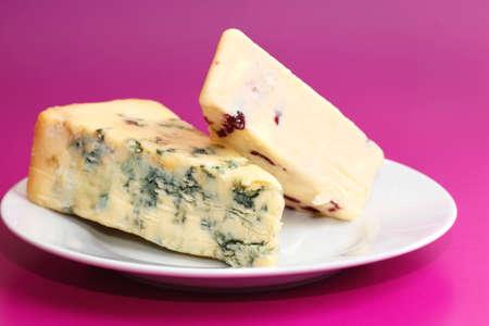 wensleydale: Dos trozos de queso azul stilton y wensleydale y ar�ndanos dispuestas en el plato de porcelana blanca aislado en un fondo de color rosado