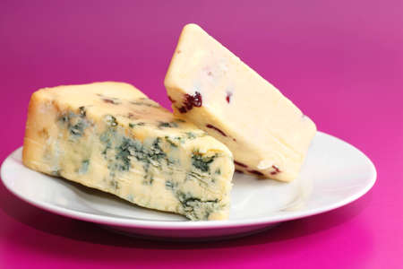 wensleydale: Two pieces of fresh cheese blue stilton and wensleydale and cranberry arranged on white porcelain plate isolated on pink background Stock Photo