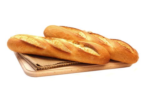 Close up of two fresh long narrow french baguettes placed on fabric mat over wooden chopping board on white background photo