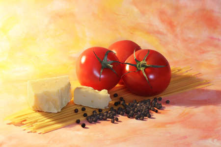 Ingredients used in Italian cuisine including red tomatoes yellow cheese fresh black pepper corns and linguine pasta backlit arranged on abstract orange background Stock Photo