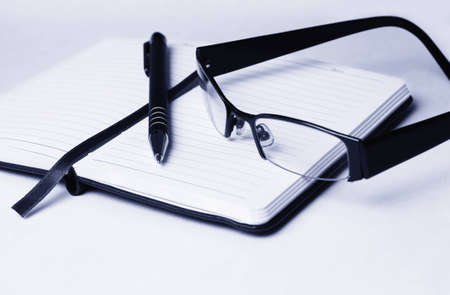 Close up of open diary topped with black pen and reading glasses isolated on gradient background