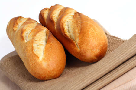 Two freshly baked french small baguettes close up on fabric place mat and white background Stock Photo - 9754178