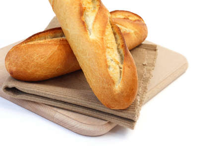 Close up of two fresh long narrow french baguettes placed on fabric mat over wooden chopping board on white background Stock Photo - 9754168