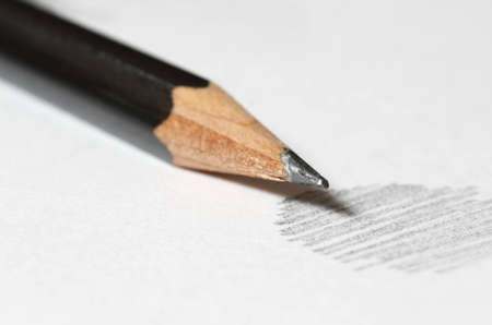 Close up of black graphite pencil on the top of white paper with abstract sketching photo