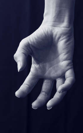 Close up of female scary grabbing hand with curled fingers under blue moon light isolated on black background