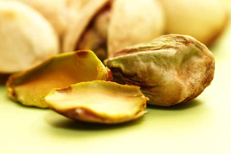 Macro of pistachios unshelled on green background Stock Photo