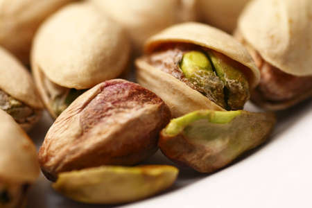 Macro of pistachio nuts in shells on white background