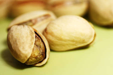 Macro of pistachio nuts in shells on green background Stock Photo