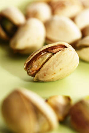 Close-up of pistachio nut in open shell on green background with more pistachios blurred in foreground Stock Photo - 9754157