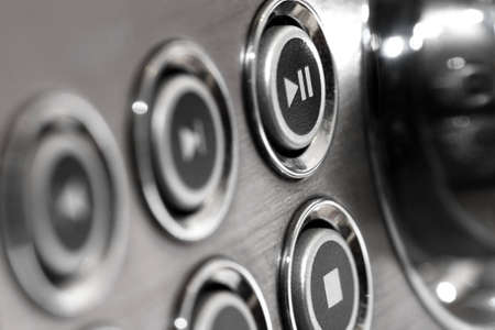 Close up of music system buttons in silver colour with play pause and stop buttons in focus