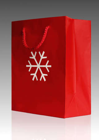 Red Christmas present paper bag with white snowflake in the middle isolated on black and white gradient background Stock Photo - 9754142