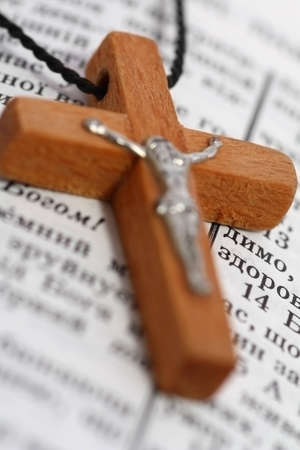 Close up of wooden cross on open Bible Stock Photo